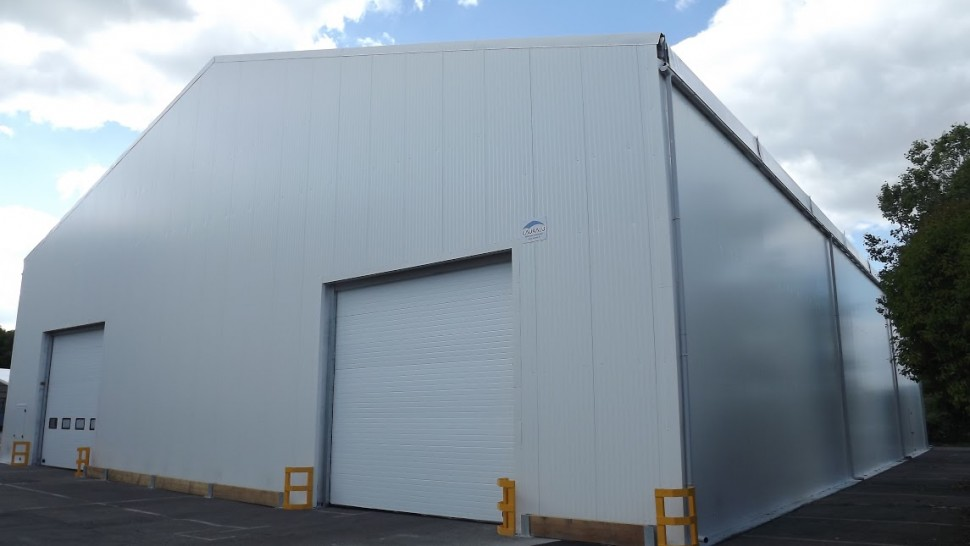 white temporary structure with two roller doors for lorries. Example of one of our Industrial Buildings temporary building hire