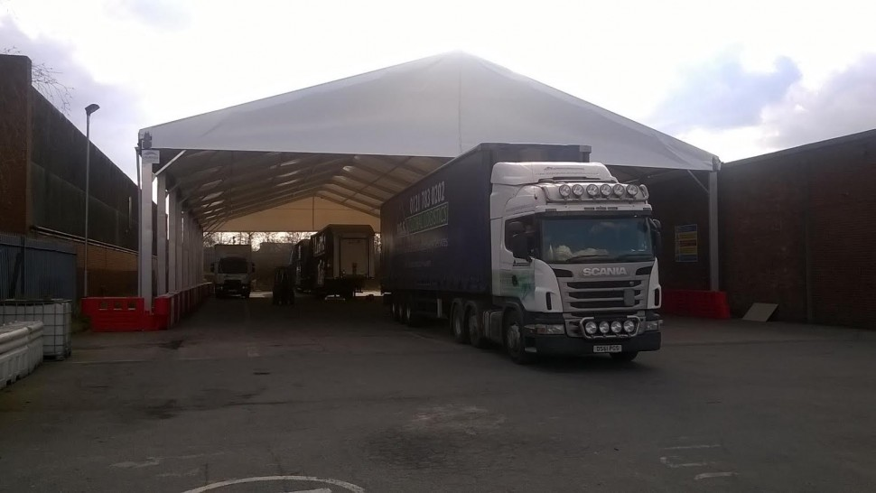 Lorry leaving a temporary Industrial canopy after being loaded